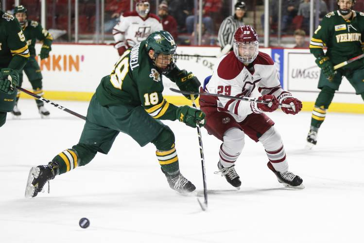 Vermont defenseman Matt O Donnell (18) moves to block UMass Amherst forward  George Mika (29) from getting the puck during a NCAA hockey game bd3a7eba5