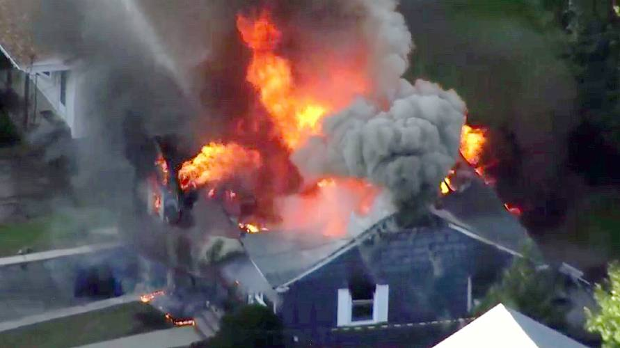 In this still image from video provided by WCVB in Boston, flames consume  the home of police officer Ivan Soto in Lawrence, Mass, a suburb north of  Boston, ...