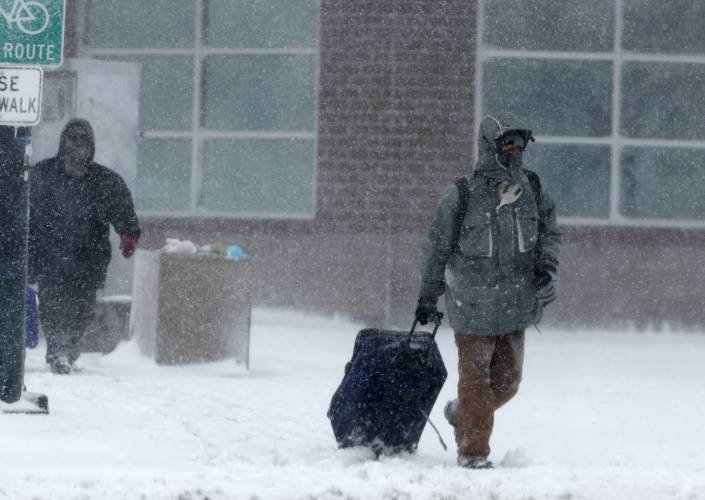 ad0383f43142 A traveler drags a suitcase as a late winter storm packing hurricane-force  winds and snow sweeps over the intermountain West Wednesday. AP PHOTOi