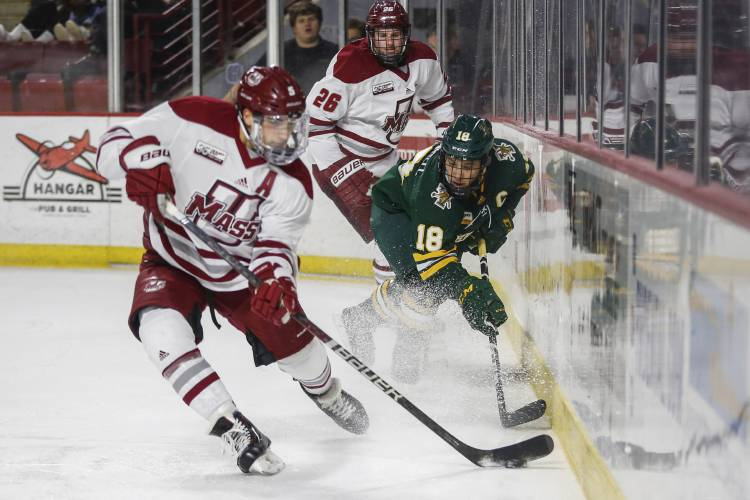 UMass Amherst defenseman Mario Ferraro (5) moves the puck away from Vermont  defenseman Matt O Donnell (18) during a NCAA hockey game 2f2058034